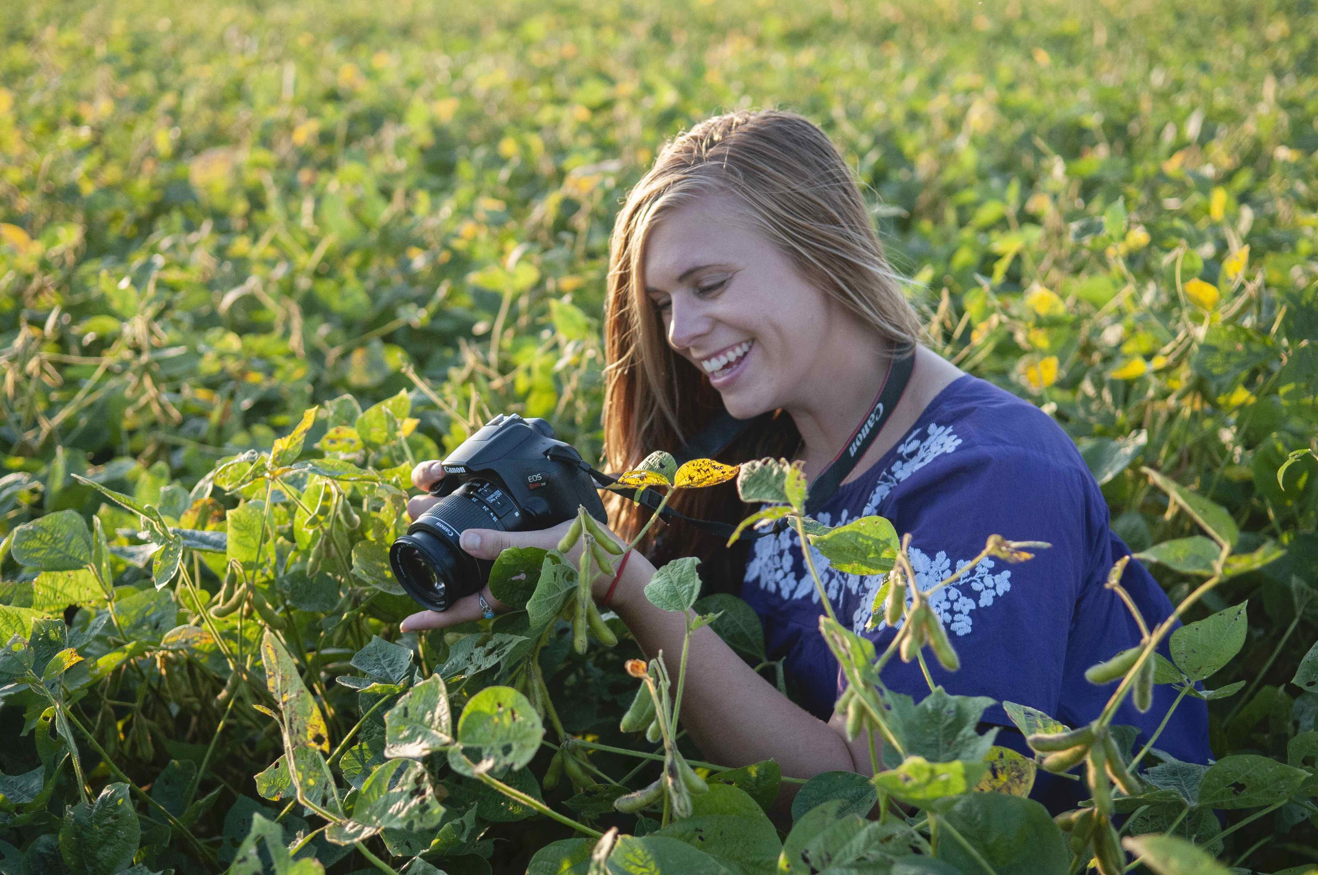 Image of a student in a field with camera.